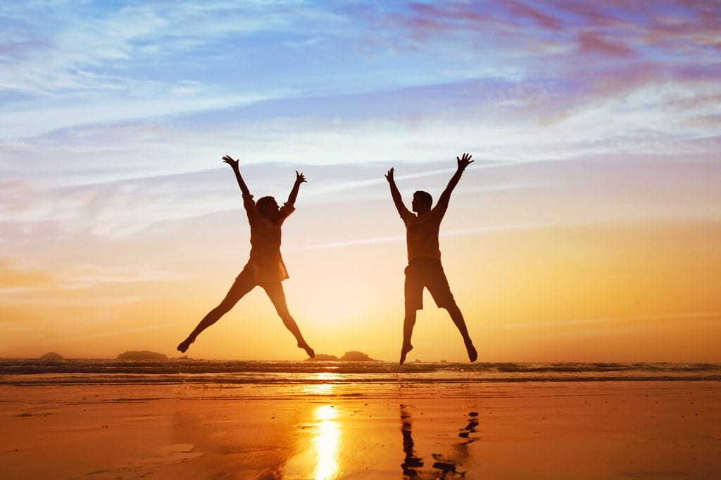 happy couple jumping on the beach at sunset